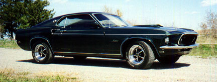 A black 1969 Ford Mustang Mach 1 with white stripe